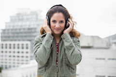 Content gorgeous brunette in winter fashion listening to music Stock Images
