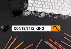 Content is king concept. On a black table colorful pencils and a computer keyboard with a mobile phone Stock Photo