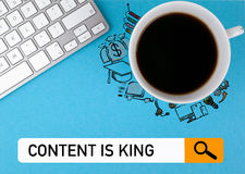 Content is king concept. On a blue background coffee mug and computer keyboard.  Royalty Free Stock Image