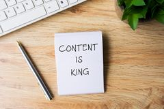 Content Is King. Word written on notepad with pen, computer keyboard and flower on top of wooden table stock images