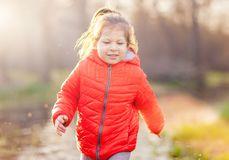 Little charming girl in spring woods. Content little girl in red coat having fun in spring park with bright sunlight Royalty Free Stock Photography