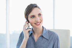 Content lovely businesswoman phoning with her smartphone sitting at her desk stock image