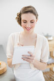 Content lovely woman standing in her kitchen writing a shopping list Stock Photography