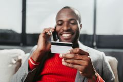 Content man connecting by mobile phone. Portrait of smiling guy sitting on couch and communicating by cellphone. Focus on bankcard in his arm Stock Photo