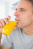 Content man drinking orange juice in kitchen. At home Royalty Free Stock Images