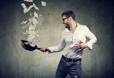 Content man with frying pan full of dollar bills stock photography