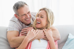 Content man hugging his wife on the couch Stock Images