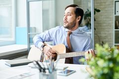 Content man playing guitar at work stock photography