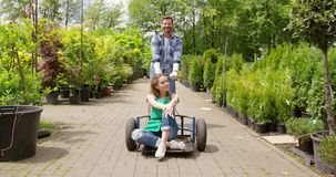 Content man riding girl in cart in garden stock footage