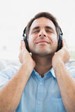 Content man sitting on sofa listening to music with eyes closed Stock Image