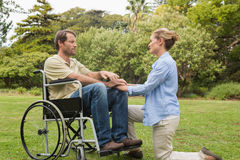 Content man in wheelchair with partner kneeling beside him Royalty Free Stock Image