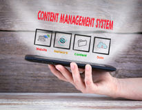 Content Management System concept. Tablet computer in the hand. Old wooden background Stock Images