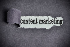 Content marketing word under torn black sugar paper Royalty Free Stock Photos
