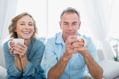 Content middle aged couple sitting on the couch having coffee. Smiling at camera at home in the living room Royalty Free Stock Images