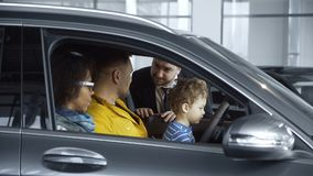 Multiethnic family in shop choosing car stock images