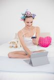 Content natural brown haired woman in hair curlers shopping online with her tablet pc Stock Image
