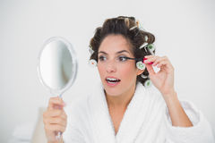 Content natural brunette applying mascara Stock Image