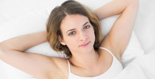 Content peaceful woman looking at camera lying on her bed Stock Photos