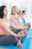 Content pregnant women meditating in yoga class Stock Images