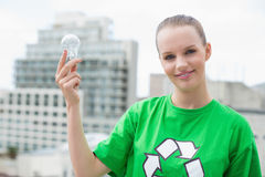 Content pretty environmental activist holding a light bulb Stock Photography