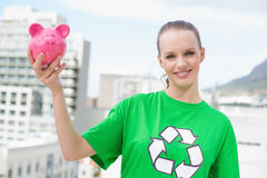 Content pretty environmental activist holding a piggy bank Stock Photography