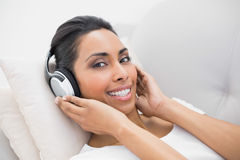 Content relaxing woman listening to music lying on couch Stock Image