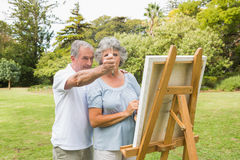 Content retired woman painting on canvas with husband Royalty Free Stock Images