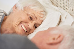 Content senior couple smiling warmly at each other in bed Stock Images