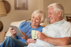 Content senior couple using a digital tablet on their sofa. Content senior couple talking and relaxing together while sitting on a sofa in their living room at Stock Photography