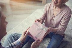 Old man and woman holding gift box with joy Stock Image