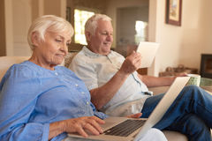Content seniors browsing the internet from their living room sofa stock photography
