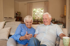 Content seniors reading text messages at home on their sofa Stock Images
