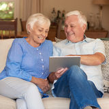 Content seniors using a touchscreen tablet on their couch Royalty Free Stock Photography