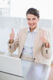 Content smart brown haired businesswoman giving thumbs up Royalty Free Stock Photos