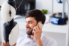 Content smiling man talking on cellphone. Share positivity. Positive handsome man holding model printed on 3d printer and talking on cellphone while expressing stock photography
