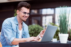 Content smiling man using laptop. Full of gladness. Positive smiling handsome man sitting at the table and using laptop while resting in the cafe stock photo