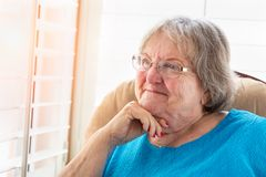 Content Senior Woman Gazing Out of Her Window Stock Photos