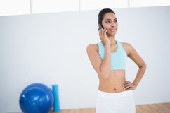 Content smiling woman in sportswear phoning with smartphone Stock Image