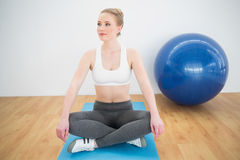Content sporty blonde sitting cross legged on exercise mat Royalty Free Stock Image