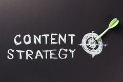 Content strategy. Handwriting of content strategy topic with dart and sketching target Royalty Free Stock Photo