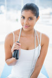 Content toned brunette sitting on floor with skipping rope Royalty Free Stock Images