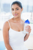 Content toned brunette sitting on floor with sports bottle Royalty Free Stock Image