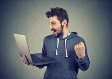 Content victorious man with laptop. Excited young man holding laptop and looking happy winning with fast upgrade Royalty Free Stock Photography