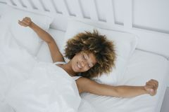 Content woman awakening in bed Stock Photo