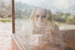 Content woman with coffee cup looking through window Royalty Free Stock Photos