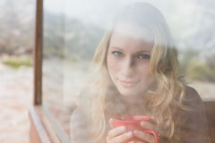 Content woman with coffee cup looking through window Stock Photo