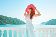 Content woman enjoying luxurious resort. Young woman suntanning on terrace looking happy with sea in Greece stock images
