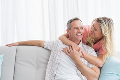 Content woman hugging his husband on the couch Royalty Free Stock Image