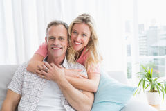 Content woman hugging his husband on the couch Stock Images