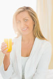 Content woman looking at camera enjoying a glass of orange juice Royalty Free Stock Photography